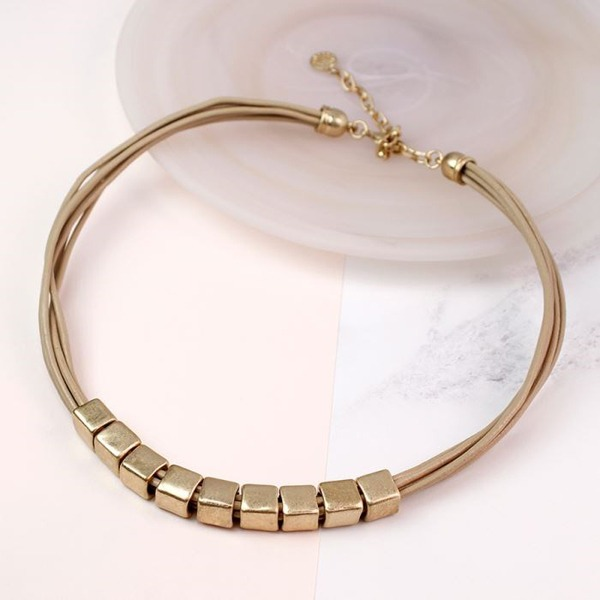 Worn Gold Tube Necklace On Leather
